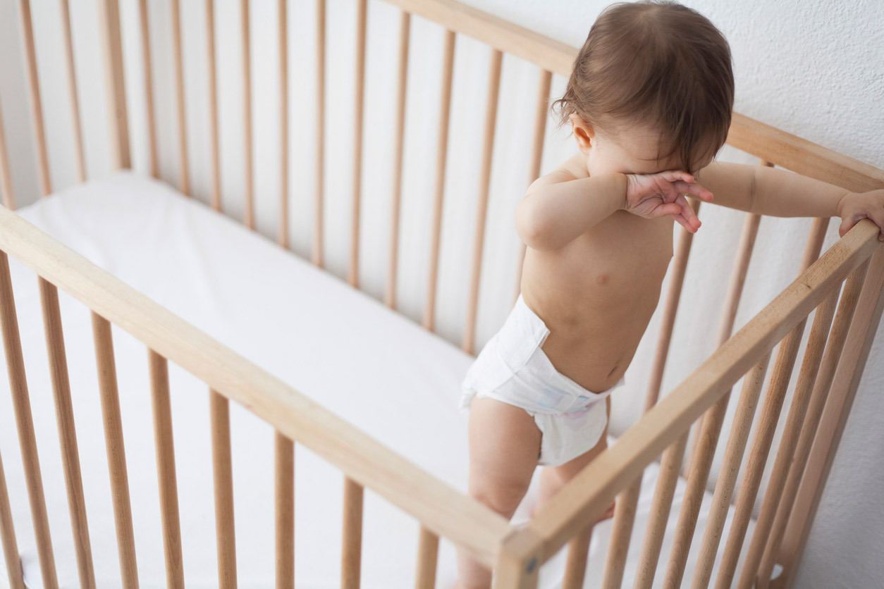 Baby wearing only a diaper standing in a crib rubbing their eyes