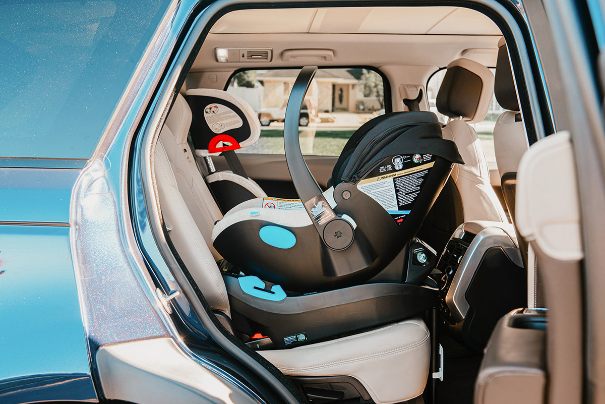 Blue SUV with rear passenger-side door open, a black Clek infant rear-facing car seat is installed in the backseat.