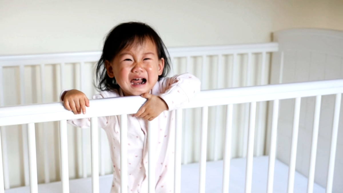 crying asian baby standing in a white crib with arms over the railing