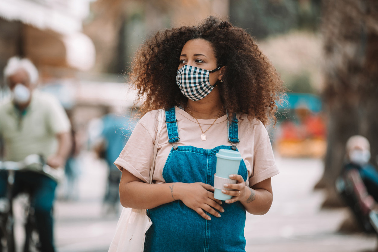 Expecting woman walking outside wearing a protective cloth mask and carrying a coffee cup.